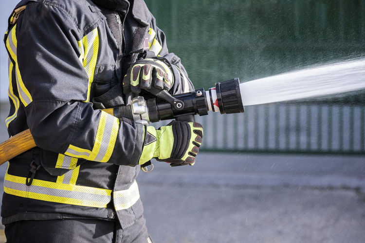 Midsection of firefighter holding fire hose outdoors
