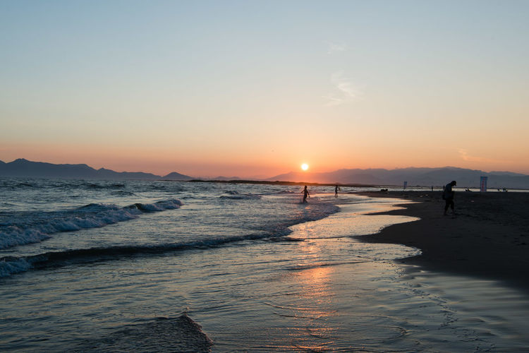 Beach Beauty In Nature Bright Horizon Over Water Incidental People Land Leisure Activity Lifestyles Nature Orange Color Outdoors Real People Scenics - Nature Sea Silhouette Sky Sun Sunset Tranquil Scene Tranquility Water Wave