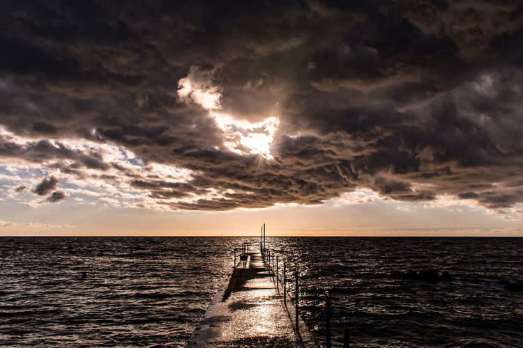 Pier In Sea Against Cloudy Sky At Sunset
