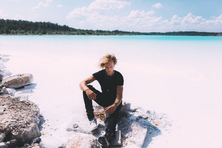 Blond curly guy is sitting on the stone around crystal clear water. Blond trendy hairstyle. Summer time, clear water, clear sky. Beach Beauty In Nature Day Holiday Land Leisure Activity Lifestyles Nature One Person Outdoors Real People Scenics - Nature Sea Sky Tranquility Vacations Water Young Adult