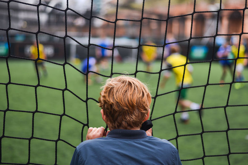 Rear view of boy standing on soccer field