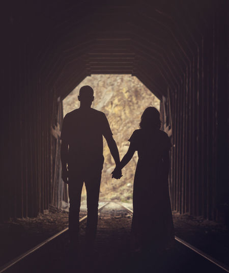 Rear view of silhouette couple holding hands while standing on railroad track in tunnel