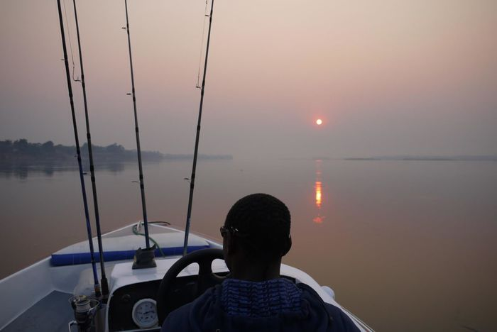 Atmosphere Atmospheric Mood Beauty In Nature Fishing Nature Non-urban Scene Scenics Sun Sunrise Tigerfish Tourism Tourist Tranquil Scene Travel Destinations Vacations Water Zambezi River