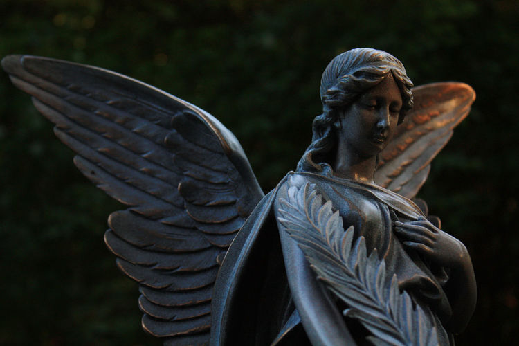 Low Angle View Of Angel Statue At Graveyard