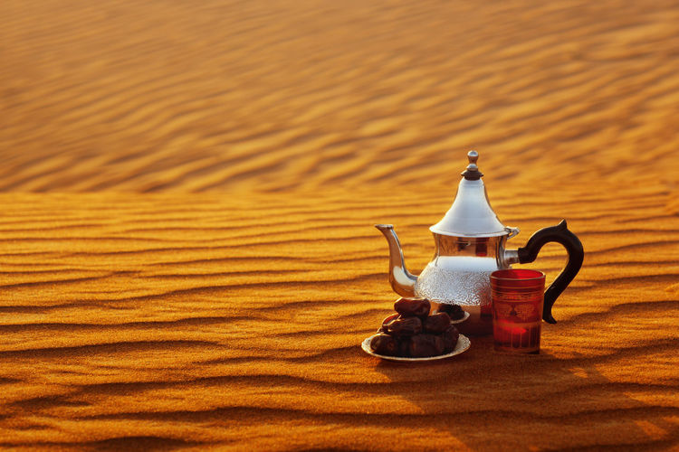 Arabian teapot, cup and dates in the desert at a beautiful sunset symbolizing ramadan