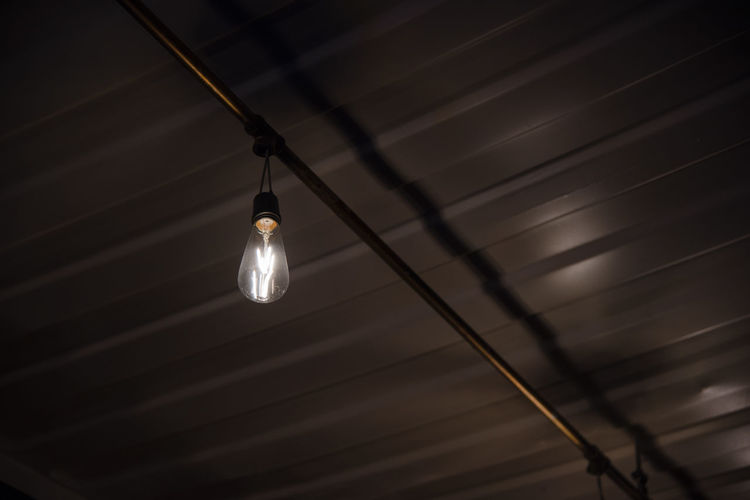 Low angle view of light bulb hanging at night