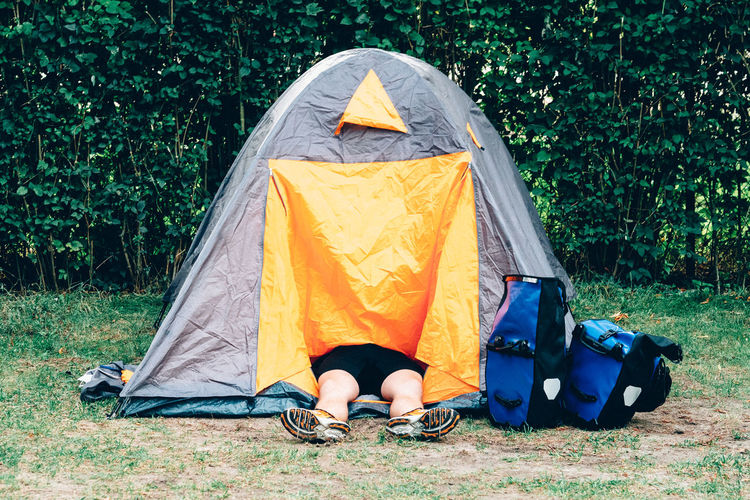 Low section of person resting in tent on field at campsite