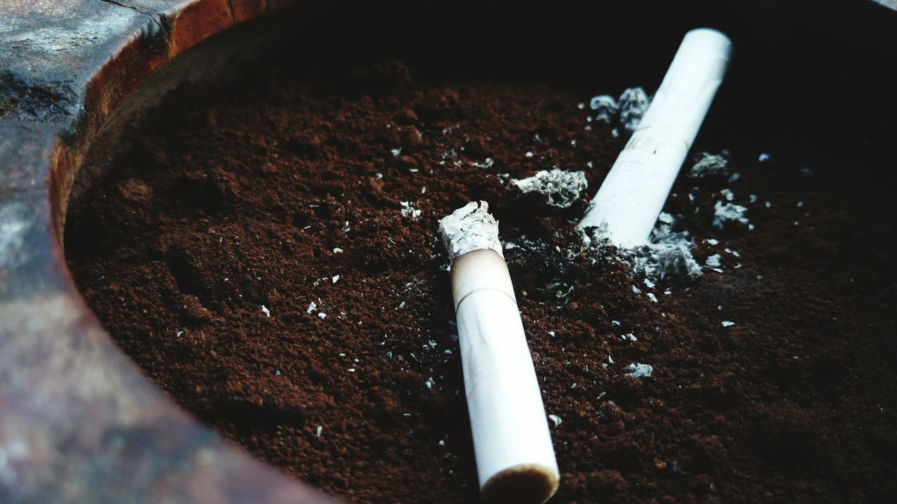 Close-Up Of Cigarette Butts On Ground Coffee