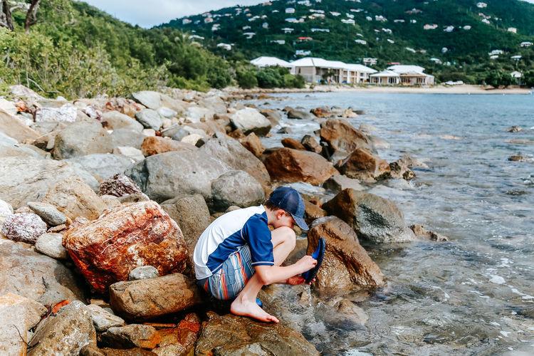 Man sitting on rock at beach