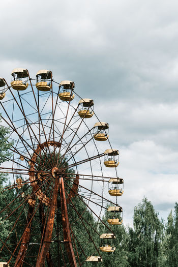 Low angle view of abandoned ferris wheel against sky