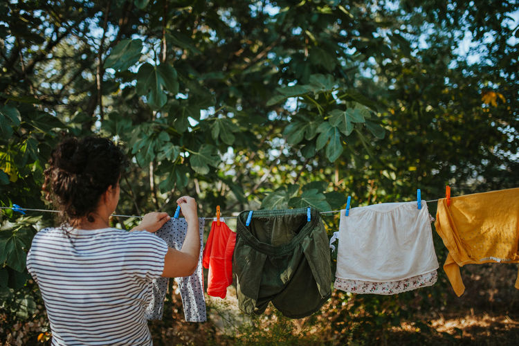 Rear view of woman drying clothes