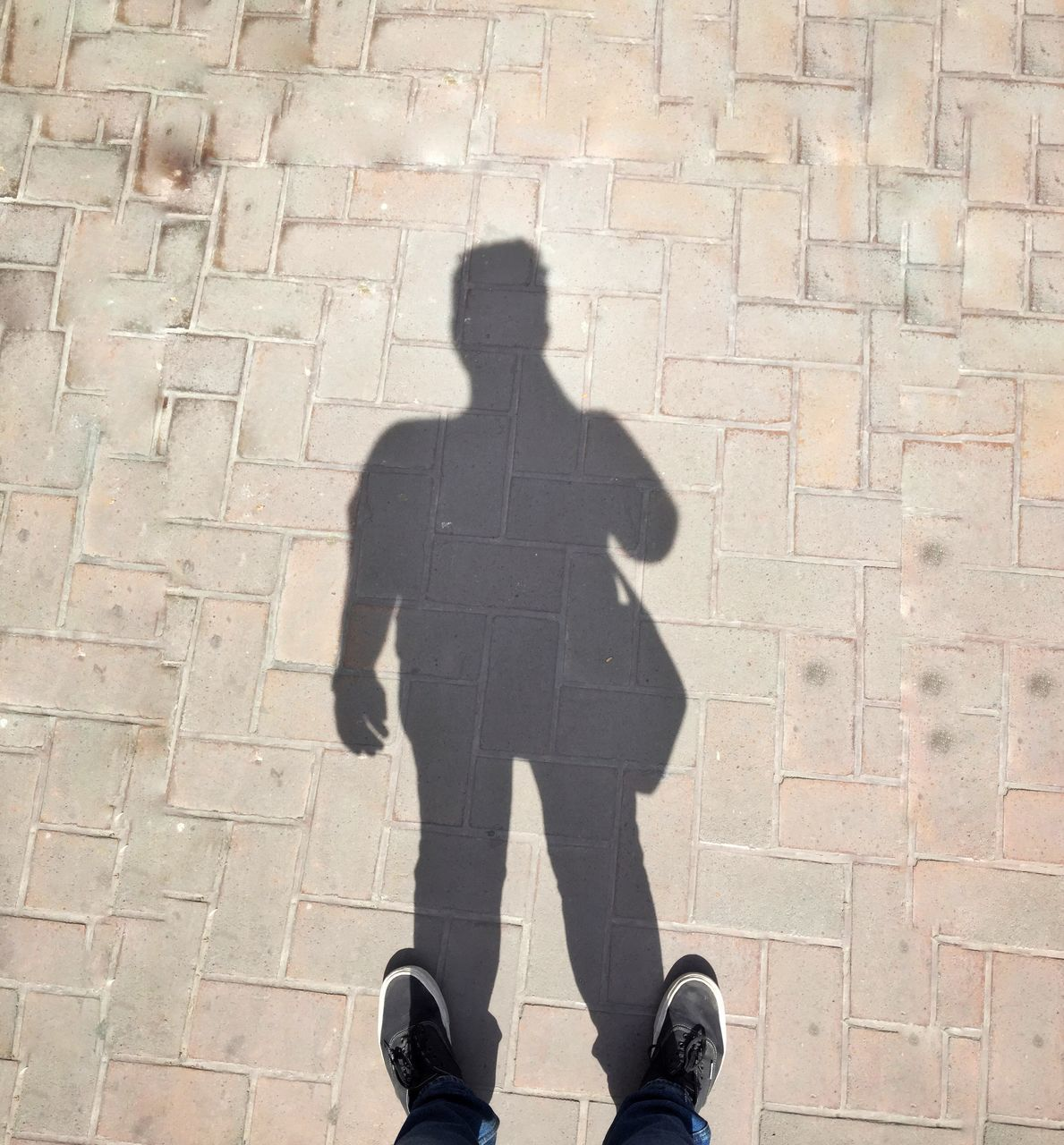 LOW SECTION OF MAN STANDING ON FOOTPATH BY STREET
