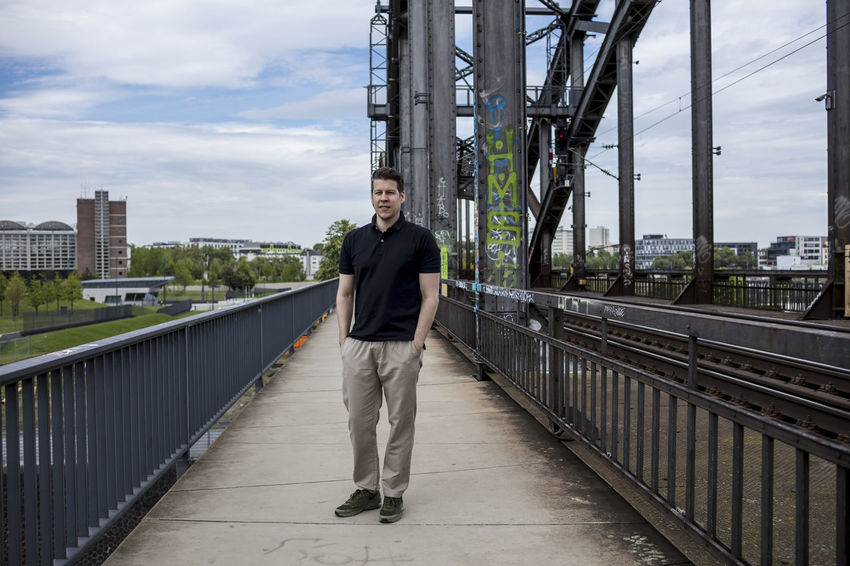 Man standing on a bridge in Frankfurt near railway tracks. City Khaki Pants Long Shot Looking At Camera Man Railing Standing Bridge Buildings Caucasian Ethnicity Causal Clothing Day Golf Shirt Good Looking Hands In Pockets Handsome Male One Person Outside Portrait Posing Railway Track Short Sleeved Summer Urban