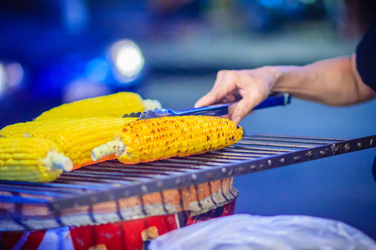 Close up hand of street food vendor while grilling for mixed sweet corn butter. Cook is grilling and sprinkling salt, sugar and butter to the grilled sweet corn on the electric stove. Grilled Corn Khao San Rd Khao San Road KhaoSan Khaosan Rd. Khaosandroad Grilled Corn On The Cob Grilled Cornes Khao San Khao San Knok Wua Khao San Rd. Khaosan Road Khaosanroad Night Market Night Market In Thailand Sprinkling Salt