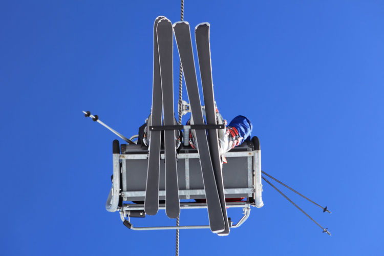 Directly below of people traveling in ski lift against clear blue sky