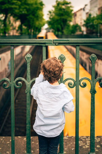 Little boy watching subway trains from a bridge Boys Casual Clothing Childhood Childhood Memories Day Green Color Ideal World Leisure Activity Lifestyles Memories One Person Railing Real People Rear View Standing Subway Three Quarter Length Toddler  Train Tracks