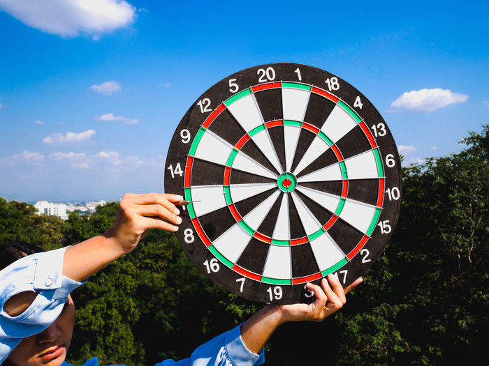 Close-up of woman holding dartboard against sky