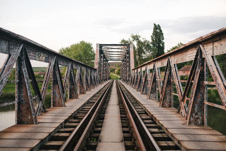 Footbridge over railroad tracks against sky