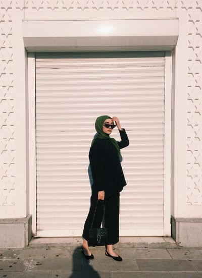 Full length of woman photographing with closed door