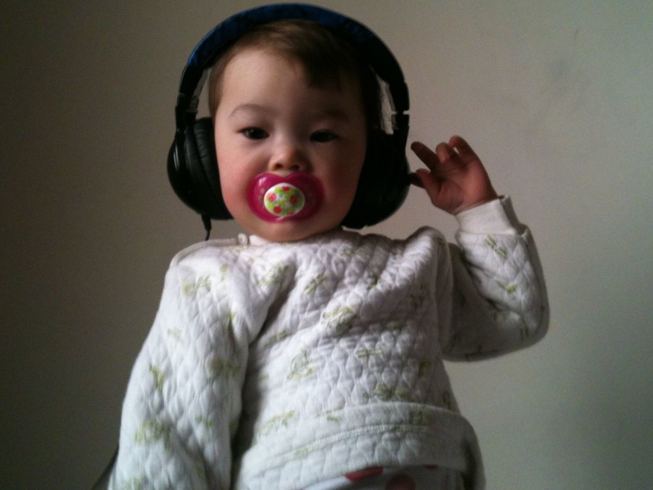 Cute Baby Girl Listening Music From Headphones Against Wall