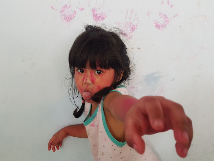 Portrait of messy girl sticking out tongue against wall during holi