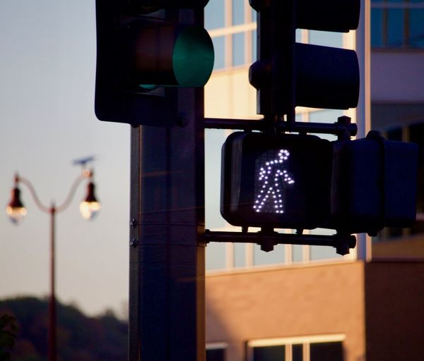 Close-up of road signal on street against sky