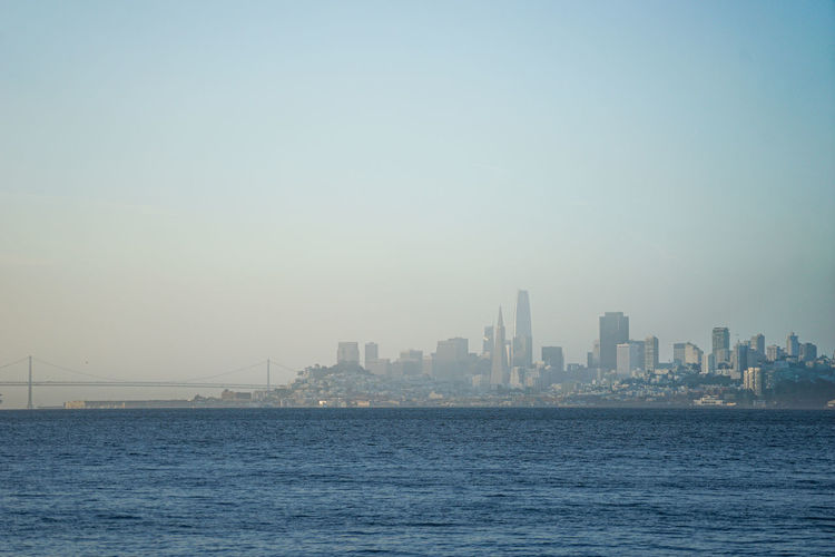Sea and buildings in city against clear sky