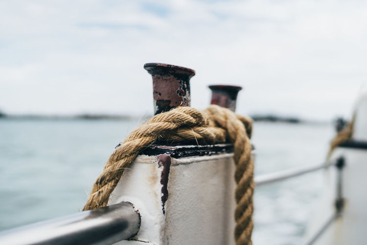 Close-up of rope tied to post of boat
