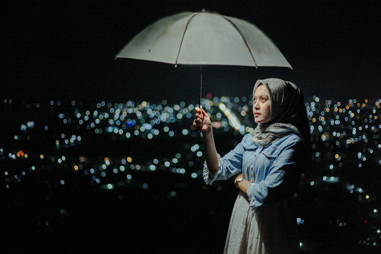 Woman holding umbrella while standing at night