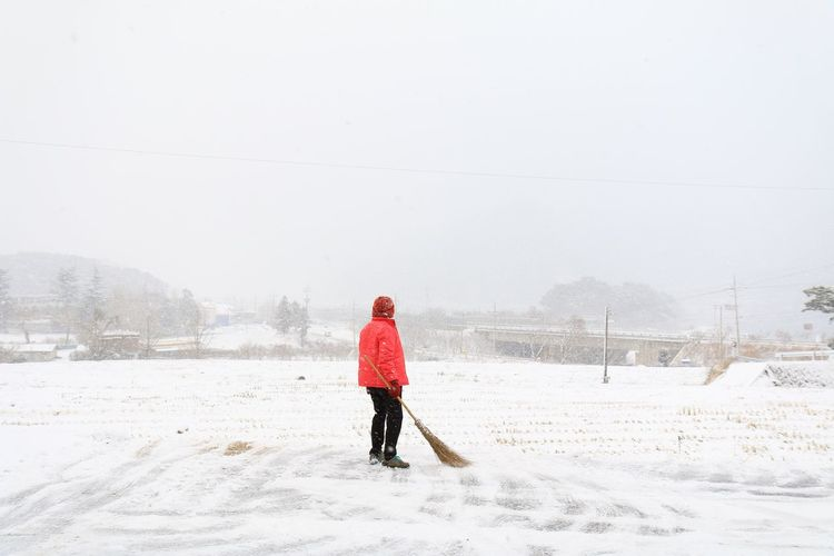 Rear view of person holding broom while standing on snowy field
