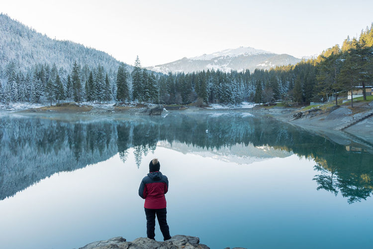rear view of young latin woman standing on a rock looking to the lake Beauty In Nature Clear Sky Day Full Length Lake Leisure Activity Lifestyles Mountain Mountain Range Nature One Person Outdoors People Real People Rear View Reflection Scenics Sky Standing Tranquil Scene Tranquility Tree Water Women