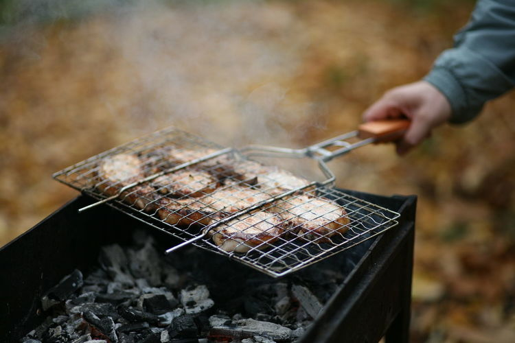 Cropped hand of man preparing food on barbecue grill