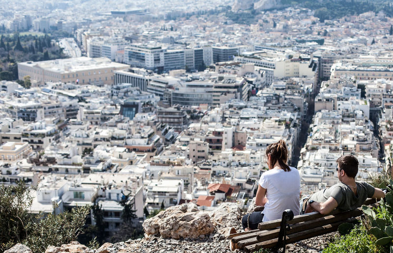 Couple sitting on bench on top of rock looking at city