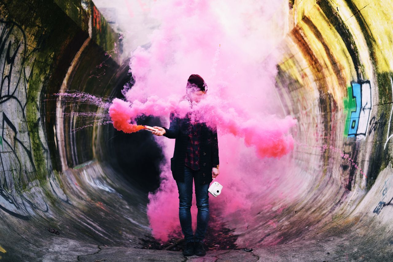 Man holding smoke bomb and camera while standing in tunnel