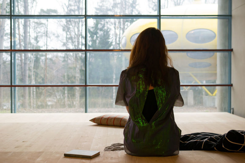New edit. Architecture Book Casual Clothing Day Floor Focus On Foreground Glitter Green Interior Leisure Activity Lifestyles Long Hair Lounge Meditating Modern Peaceful Pillow Red Hair Sitting Sparkly Still Life View From Behind Waiting Woman Wood - Material