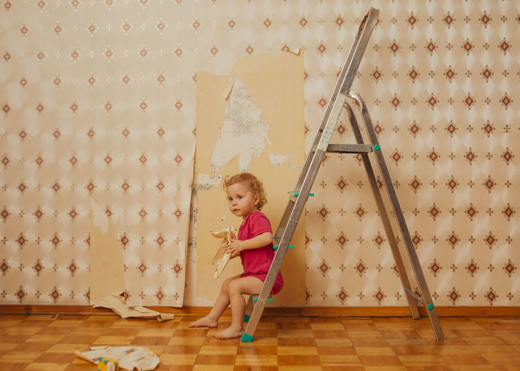 Child tear off the wallpaper from the wall in the room, little mother's helper