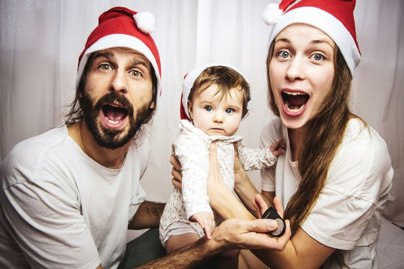 young family with santa hats having fun at christmas time Mouth Open Surprised Xmas Christmastime Family Christmas Spirit Christmas Is Coming Santa Hat EyeEm Selects Christmas Family Celebration Father Fun Childhood Hat Togetherness Portrait Holiday - Event Parent Looking At Camera Holiday Moments