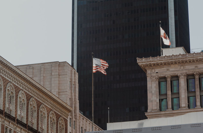 Low Angle View Of Flags Against Buildings