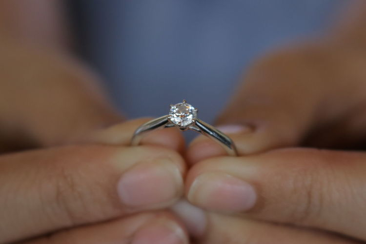Cropped hand of person holding wedding ring