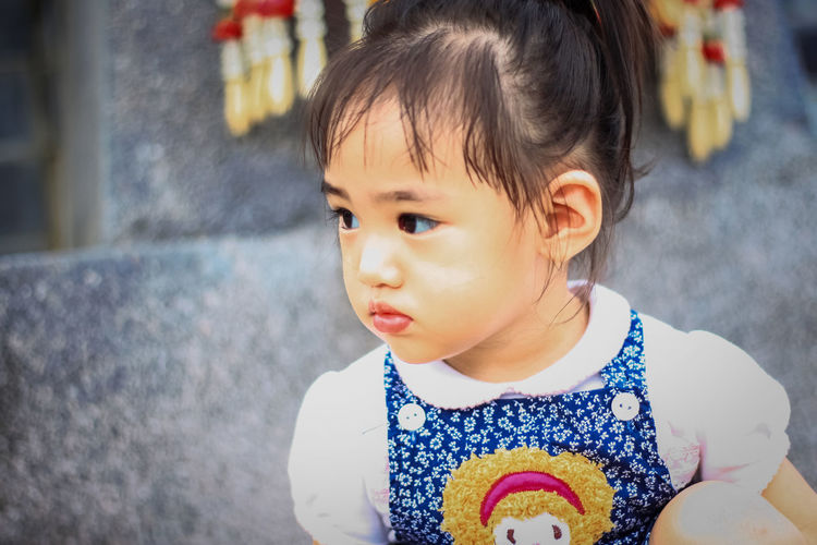 Cute girl looking away against wall