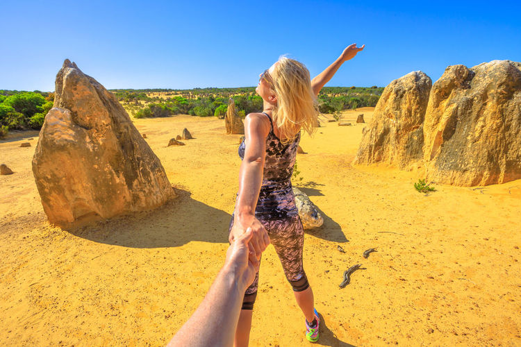 Rear view of woman holding hands of man while standing outdoors