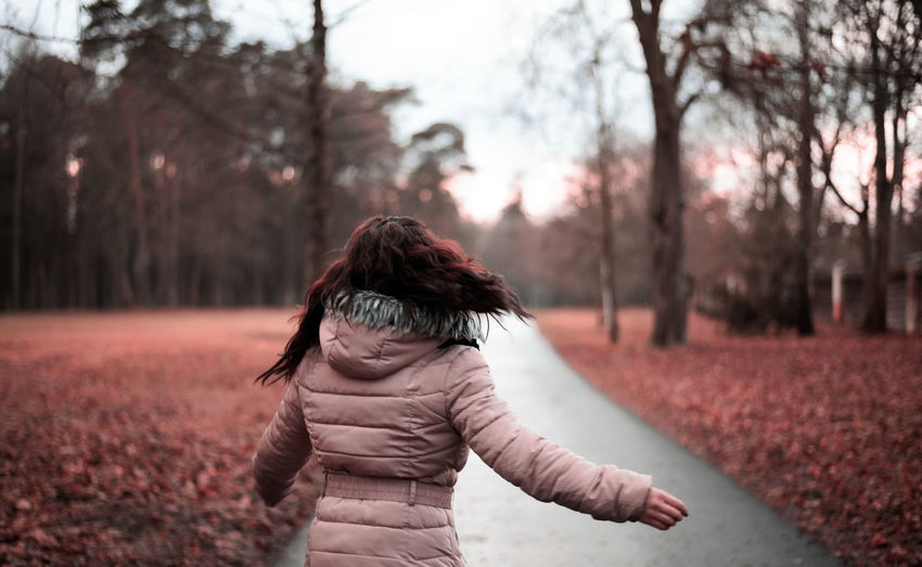Rear view of woman standing in park during winter