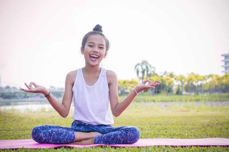 Yoga enhances concentration and mood. Casual Clothing Child Childhood Day Emotion Focus On Foreground Front View Full Length Girls Grass Hairstyle Happiness Innocence Leisure Activity Lifestyles Looking At Camera Nature One Person Outdoors Portrait Sitting Smiling