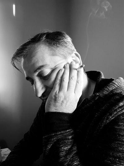 Close-up of sad mature man holding cigarette