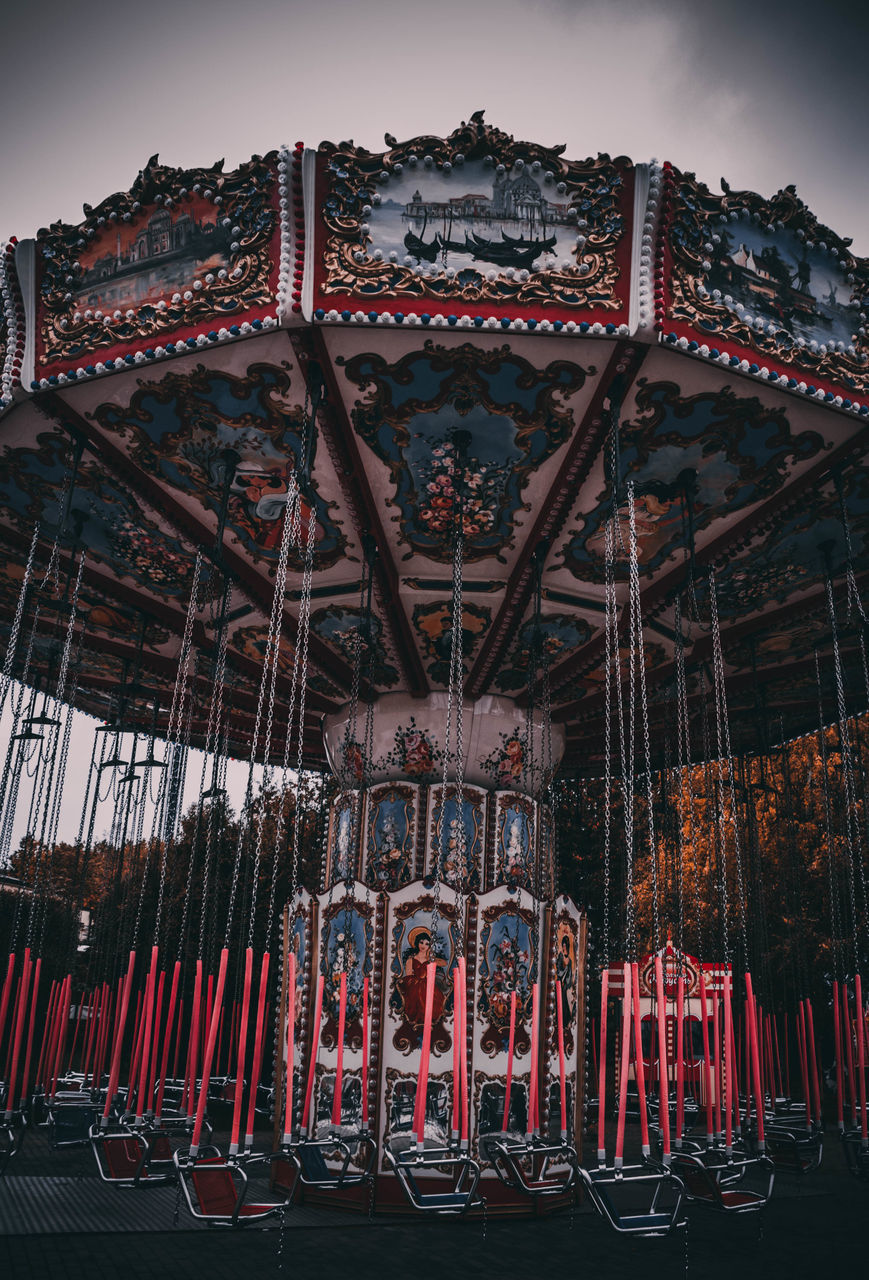 LOW ANGLE VIEW OF ILLUMINATED CAROUSEL AT AMUSEMENT PARK