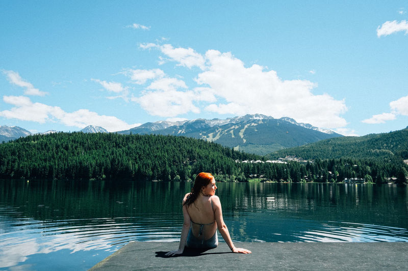 Rear view of woman sitting against calm lake