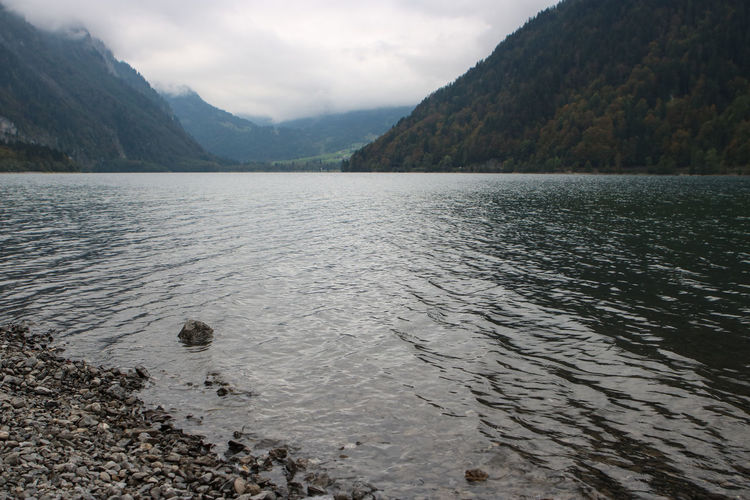Scenic shot of calm lake in front of mountains