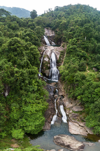 Scenic view of waterfall against rock formation in forest