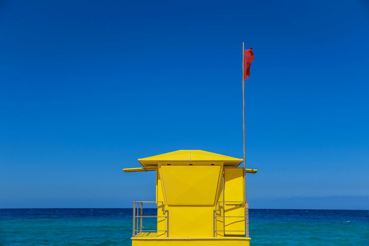 Lifeguard Tower in Coralejo beach, Fuerteventura, Canary Islands Spain. Colorful postcard from tropical vacation. Yellow little house with blue sky and ocean in background Travel holiday summer concept Ami Architecture Art Atlantic Attractive Bay Beach Beautiful Breathtaking Bright Building Chair Clouds Cute Dangerous Exotic Holidays Horizon Hut Landscape Leisure Lifeguard Station Lifestyle Modern Nature Nobody Outdoor Paradise Park Protection Red Relax Relaxation Rescue Safety Sand Scene Sea South Station Sun Swimming Trip Typical Vacation Vibrant Water Wind Wooden