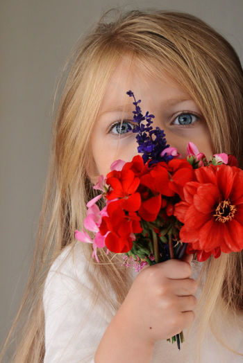 Close-up portrait of beautiful woman holding red flowering plant